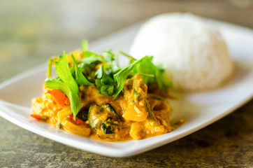 Thai food,Stir fried squid with yellow curry and cooked rice on white dish