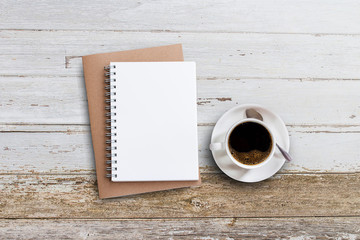 Blank notepad and coffee cup on white wooden