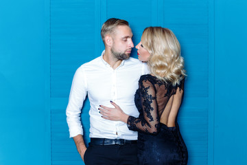 Sexy and beautiful young couple posing on blue background. Beautiful blonde Woman with Luxury Makeup, Red sexy lips