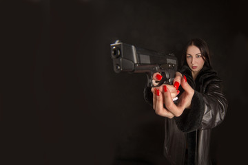 Young woman pointing a gun on black background with copyspace