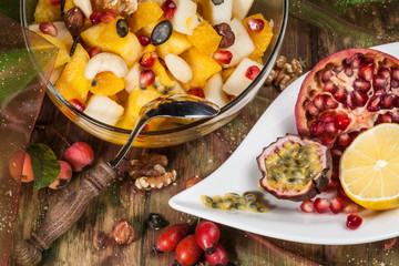 Nahaufnahme eines exotischen Obstsalats auf altem Holztisch