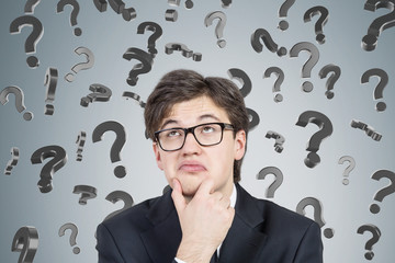 Businessman in suit and glasses and 3d question marks
