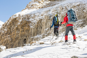 Two tourists with backpacks in snowy Himalayas, trek to the Dhaulagiri base camp, Nepal.