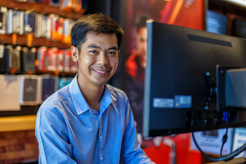Handsome young asian man using computer in office