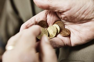 Hand einer Seniorin mit Münzgeld