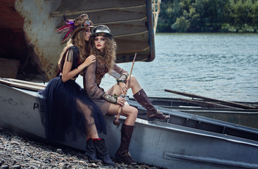 Two girls in beautiful dresses on the river.