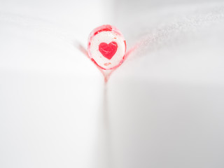 Closeup of heart shape candy cane with blurry grey fabrics backg