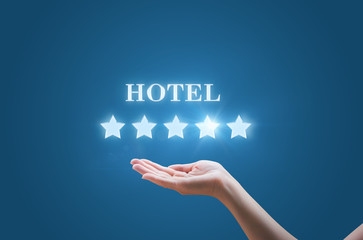 Businesswoman holding in his hand five stars and the inscription the Hotel on a blue background