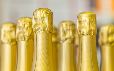 Big amount of golden champagne bottles necks and top caps at standing the light background
