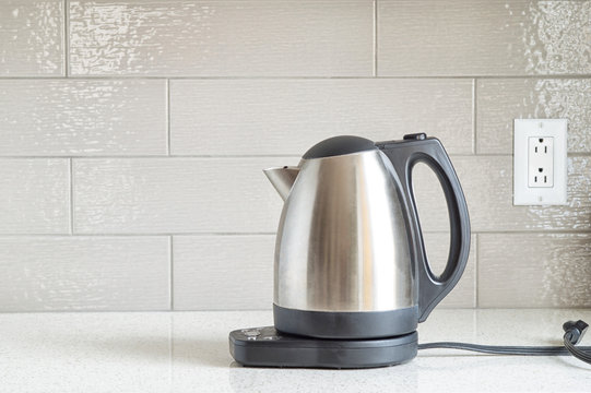 Electric stainless steel kettle on a granite counter top against