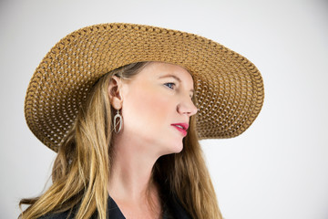 Mature Blonde Female Wearing Hat with Head Tilted Away From Camera