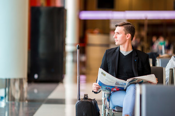Young caucasian man with newspaper at the airport while waiting for boarding. Casual young businessman wearing suit jacket.