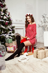girl in a red sweater sits on a toy moose near a Christmas tree.New Year concept