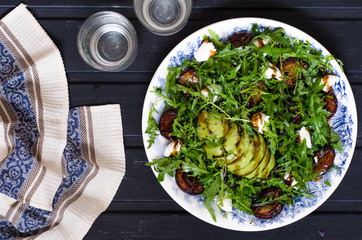 Arugula salad with goat cheese and avocado with plums