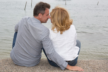 Romantic married couple on the beach sitting