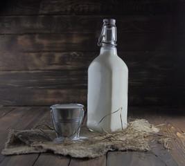 молоко в бутылке и ведре с сеном на деревянном фоне