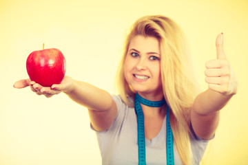 Woman holding apple showing thumb up