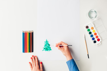 Woman painting Christmas tree with a watercolor