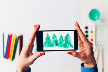 Woman take a picture of Christmas Trees