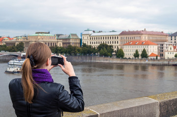 Pretty young woman taking photos with small camera. Back view of girl making picture