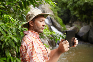 People and technology concept. Side view of bearded ecologist in panama hat taking photographs or shooting video of wild nature in tropical forest using digital tablet, standing at mountain river