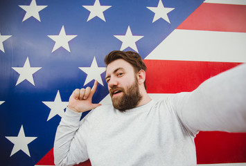 Funny bearded man smiling and taking selfie photo with American flag on the background.
