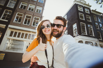 Happy young couple in love takes selfie portrait near canals in Amsterdam, Netherlands.
