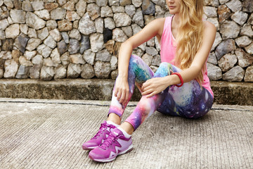 Cropped view of attractive athletic woman sitting on pavement having break during jogging workout outdoors. Blonde female runner in violet sneakers resting against stone guardrail background