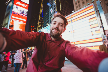 Cute funny man taking selfie on Times Square at night, Manhattan. Inspiring New York atmosphere and a handsome bearded hipster