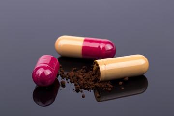 Orange antibiotics pill and capsule powder on the black background