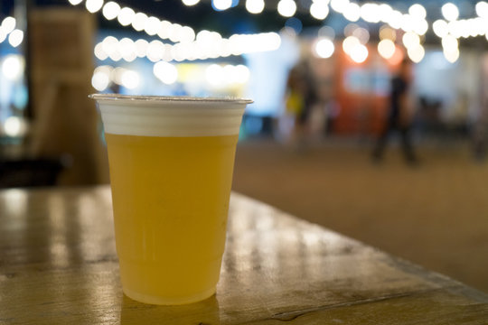 draft beer in plastic cup on wooden table at festival with bokeh light