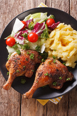 roasted duck leg with mashed potatoes side dishes and fresh salad closeup. vertical top view
