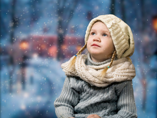 Wonderful little girl looks at the falling snowflakes, snow. Portrait