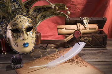 Theater concept. Vintage still life with quill and scroll near mask, old chest and glasses on red background