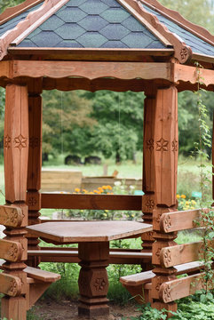 wooden gazebo in the Park on background of green trees