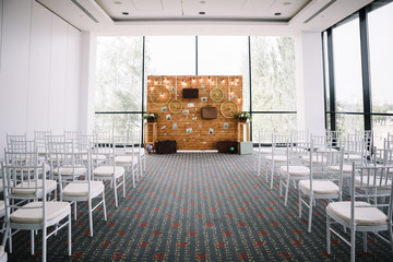 Wedding setting with white chairs for guests, a wooden wall arch in the style of travel