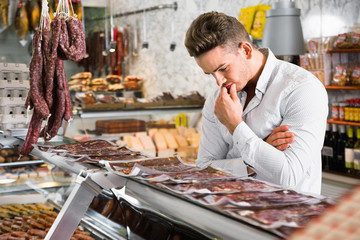 Young man choosing what kind of meat to buy