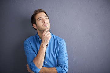 Young man portrait. Cropped shot of thoughtful man standing by the wall.