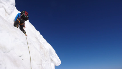 mountain climber on a steep and exposed snow slope in the French Alps near Ailefroide