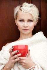 beautiful woman wrapped in a blanket with a cup in his hands