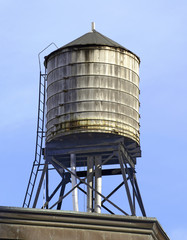 Vintage wooded water tanks on roof of apartment building in New York City hold water that is sourced from the Catskill Mountains