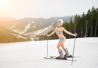 Happy beautiful naked girl skier posing on the snowy slope with ski equipment. Looking to the camera. Ski resort, ski lift, slopes and forest on background