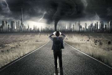 Stressful entrepreneur standing on road with storm