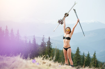 Happy woman skier is enjoying warm spring, wearing swimsuit, boots and sunglasses. Woman is holding her skis about head. Snowy mountains, forests on the background. The end of winter season. Bukovel