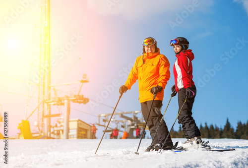 361e389417a Couple holding skis standing together at a winter resort with ski lifts and  blue sky in background. Man is wearing orange jacket