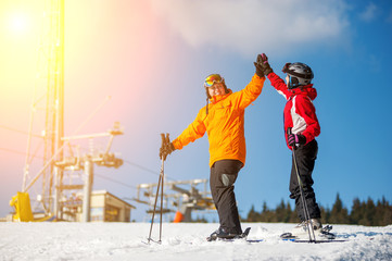 Man and woman holding hands, smiling looking at each other standing with skis on mountain top and giving each other a high five at a winter resort with ski lifts and blue sky in background