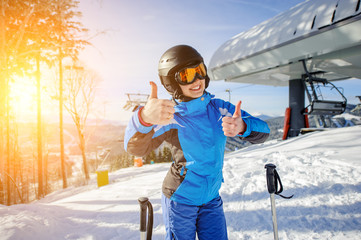 Portrait of young beautiful female skier at ski resort smiling and showing thumbs up. Winter sports concept. Woman is wearing blue jacket and blue pants, helmet and orange goggles. Bukovel, Ukraine