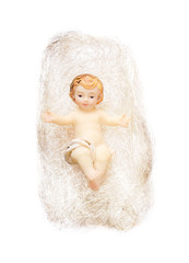 Christ child figurine in angel hair on white background. Handcrafted Child Jesus Christmas tree decoration. Antique tiny xmas tree ornament macro photo closeup from above.