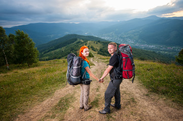 Redhead girl and guy holding hands and looking at the camera on the road in the mountain on the background of the landscaped mighty mountains, forests, hills and clouds sky