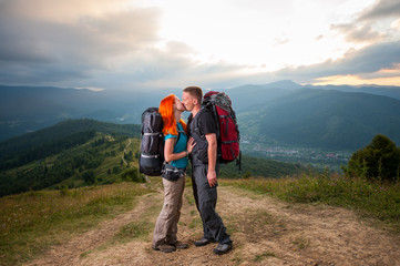 Loving couple backpackers is kissing on the road in the mountains. On the background - mighty mountains, forests, hills and clouds sky